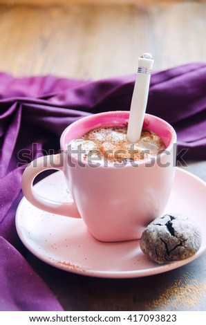 Hot chocolate with marshmallow in pink cup with saucer and shortbread on background of purple cloth, selective focus - stock photo