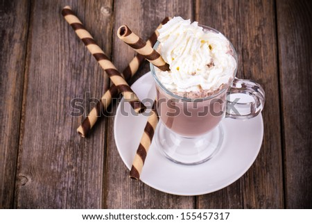 Hot chocolate with whipped cream topping, in glass with  rolled wafer. Vintage effect processing - stock photo