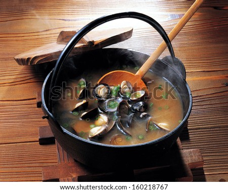 Hot clam chowder and vegetables, cooked in a pot. / Mussel soup. - stock photo