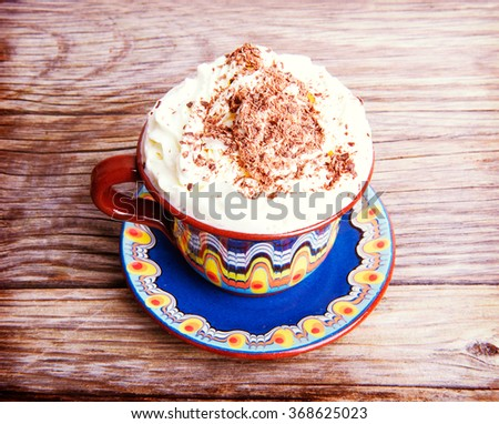 Hot cocoa drink cappuccino with whipped cream on a wooden background - stock photo
