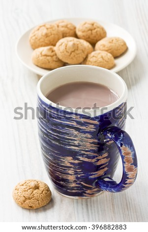 Hot cocoa drink in blue rustic mug and amaretti biscuits cookies/Hot cocoa drink   - stock photo