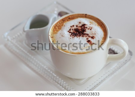 hot coffee cappuccino and cinnamon in white cup - stock photo