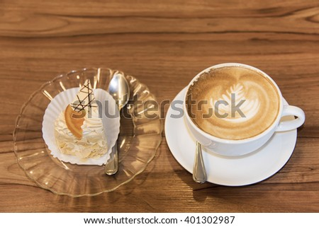 Hot coffee cup with cake on wood table. - stock photo