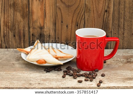 Hot coffee in red cup with sandwich on white dish and beans coffee on wooden table. for background. - stock photo