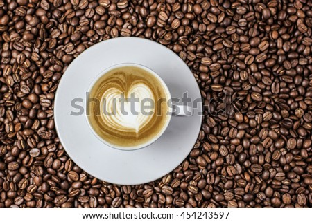Hot coffee in the coffee beans with latte art - stock photo