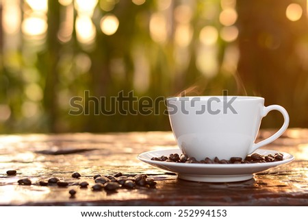 Hot coffee in the cup on old wood table with blur dark green nature background - soft focus - stock photo