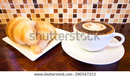 hot coffee mocha latte in white mug  and croissant on wood background at  coffee cafe - stock photo