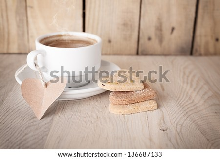 hot coffee with a not paper and heart shaped cookies on wooden background - stock photo