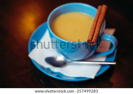 hot coffee with milk and cinnamon, a drink in a blue ceramic bowl on a dark background. winter concept bars, coffee shops, cafes and restaurants. - stock photo