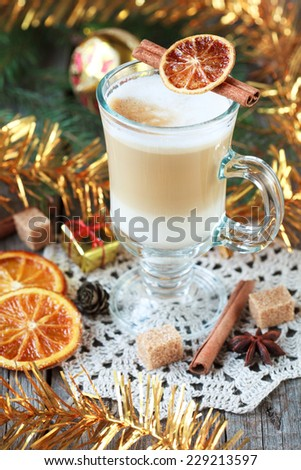 Hot coffee with milk in a glass on a wooden table with pieces of sugar, cinnamon sticks, candied orange slice and yellow Christmas tree toys. Selective focus, toned - stock photo