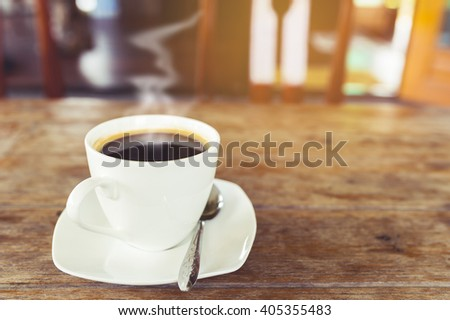 Hot coffee with smoke on wooden table in coffee shop. Vintage filter - stock photo