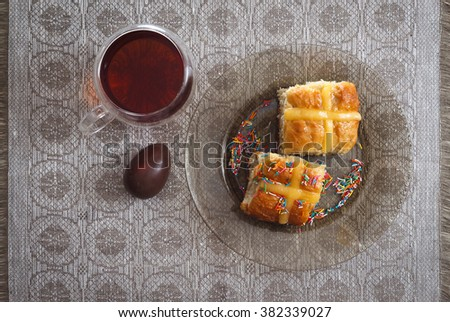 Hot cross buns, cup of tea and chocolate eggs on easter breakfast table, horizontal top view - stock photo