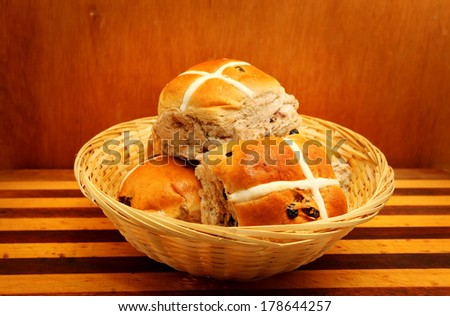 Hot cross buns in the basket on wooden background  - stock photo