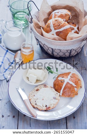 Hot cross buns on a ceramic white plate with butter and butter knife, honey and milk with basket of hot cross buns in background - stock photo