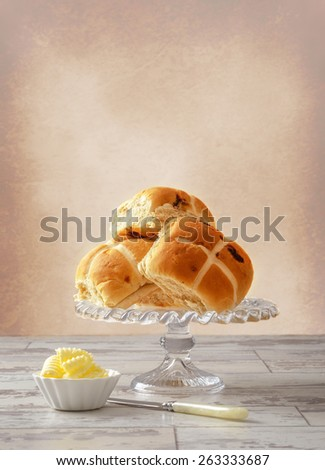 Hot cross buns with serving of butter - stock photo