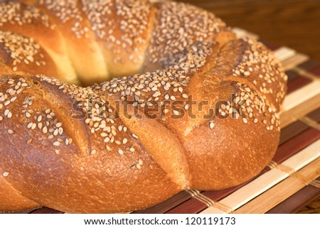 Hot crusty loaf of round Italian bread with sesame seeds - stock photo