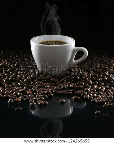 Hot cup of coffee and beans on a dark background - stock photo