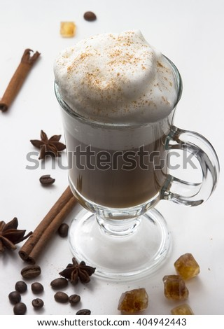 hot Cup of coffee with whipped milk foam on the white isolated background with cinnamon sticks, stars of anise and caramel sugar. The idea for the menu and the coffee shop. Cappuccino hot.  - stock photo