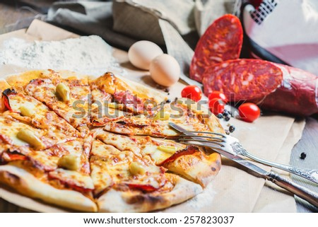 Hot delicious italian pizza with papper background on wooden table with the creative decoration of the ingredients - stock photo