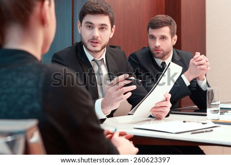 Hot discussion. Two business people in formalwear discussing something with their female colleague while sitting together at the meeting - stock photo