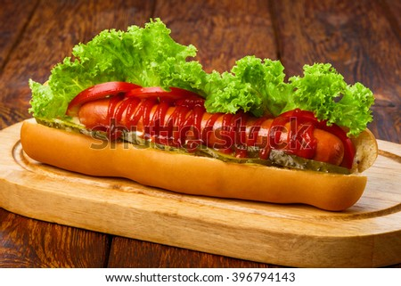 Hot dog. American fast food restaurant cuisine - hotdog with mustard, mayonnaise and ketchup with lettuce at wooden desk on the table. Tasty hotdog at wood. - stock photo