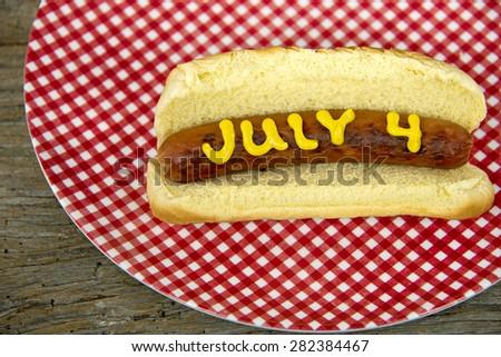hot dog and bun with mustard on red and white gingham plate for the 4th of July holiday - stock photo