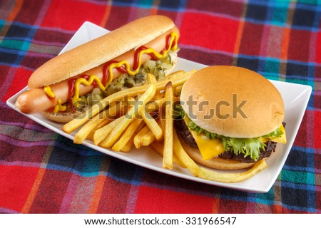 Hot dog , french fries and cheese burger on plate , fast food lunch on red fabric surface - stock photo