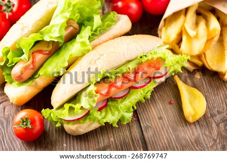Hot dog. Grilled hot dogs with mustard and ketchup on a picnic wooden table. Sandwich - stock photo