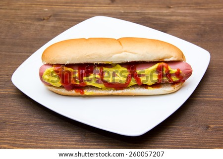 Hot dog on plate on wooden table - stock photo