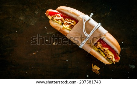 Hot dog with all the trimmings with a smoked frankfurter, pickles, salad and mustard tied in a brown paper wrapper against a black background with copyspace - stock photo