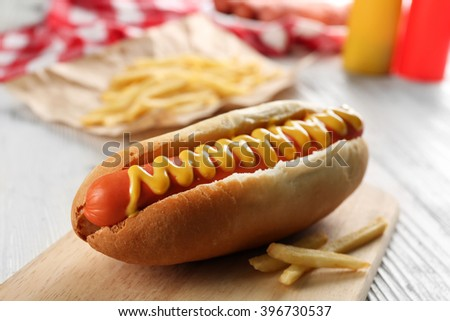 Hot dog with fried potatoes on craft paper - stock photo