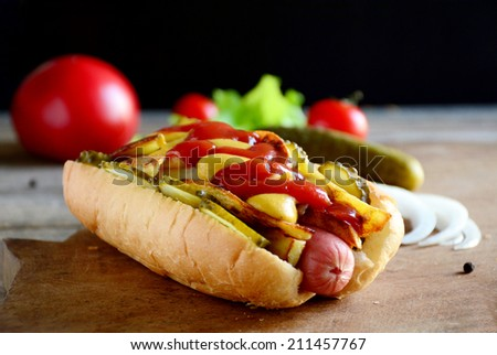Hot dog with fried potatoes, pickles, spicy mustard and sweet mild ketchup on wooden cutting board, black background. Close up fast food image - stock photo