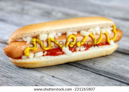 Hot dog with ketchup , yellow mustard and onion on gray wooden surface - stock photo