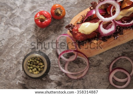 Hot dog with sausage and onions with salt red hot pepper on a brown background propki - stock photo