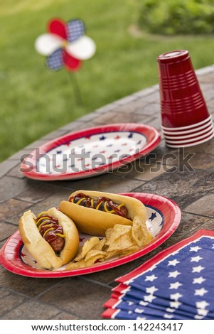 Hot dogs at a July 4th cookout are dressed with ketchup and mustard and are served with potato chips.  Selective focus was used on this image which is in a series of patriotically themed images. - stock photo