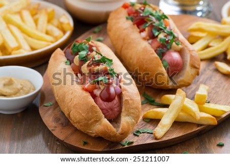 hot dogs with tomato salsa and onions on wooden board, horizontal - stock photo