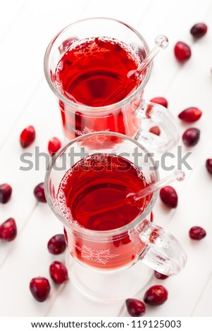 Hot drink with cranberries on white - stock photo