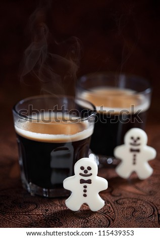 Hot espresso and white chocolate candy men, selective focus - stock photo