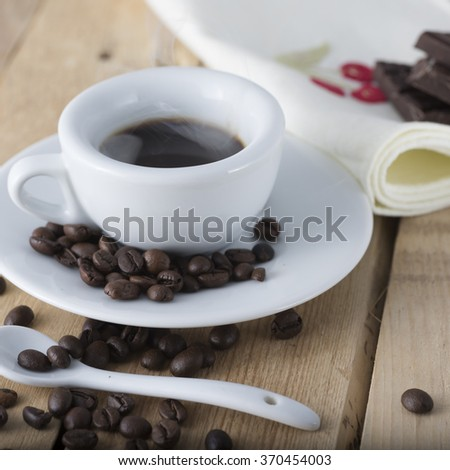hot espresso coffee in a white cup served on an old wooden table. - stock photo