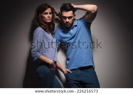 Hot fashion couple posing together, both fix their hair while looking at the camera. - stock photo