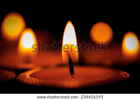 Hot flames of candles in dark room - stock photo