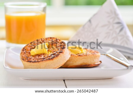 Hot fresh breakfast crumpets with butter melting on top - stock photo