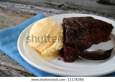 Hot fudge cake with vanilla icecream, all with a plate, spoon, and napkin. - stock photo