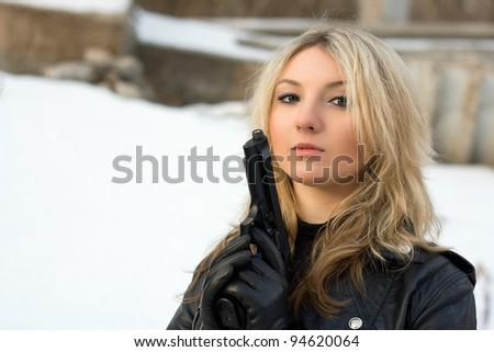Hot girl holding a gun against the snow - stock photo