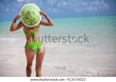 Hot green bikini woman with slim sexy body standing from behind on tropical white sand beach in Caribbean paradise looking over the perfect turquoise ocean. Luxury living vacation destination.  - stock photo
