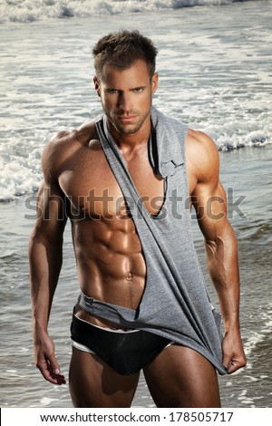 Hot handsome young man with fit muscular body in front of ocean water - stock photo