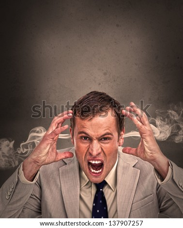 Hot headed business man yelling on brown background with copy space - stock photo
