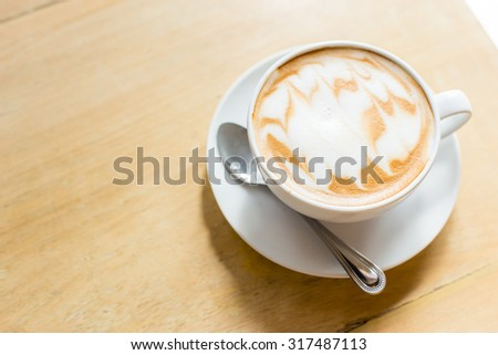 Hot latte art coffee cup on wooden table, vintage and retro style - stock photo