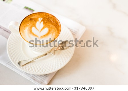 hot latte art coffee with newspaper on wooden table, vintage and retro style - stock photo