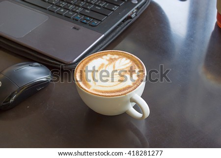 Hot latte coffee cup in a white cup on a table laptob in coffee shop. selected focus - stock photo